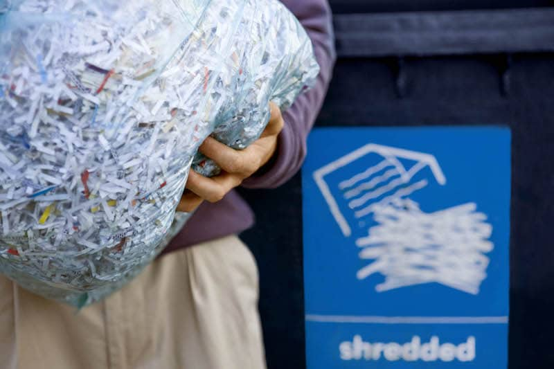 Close up of a person holding a bag of shredded documents in front of a shredded sign