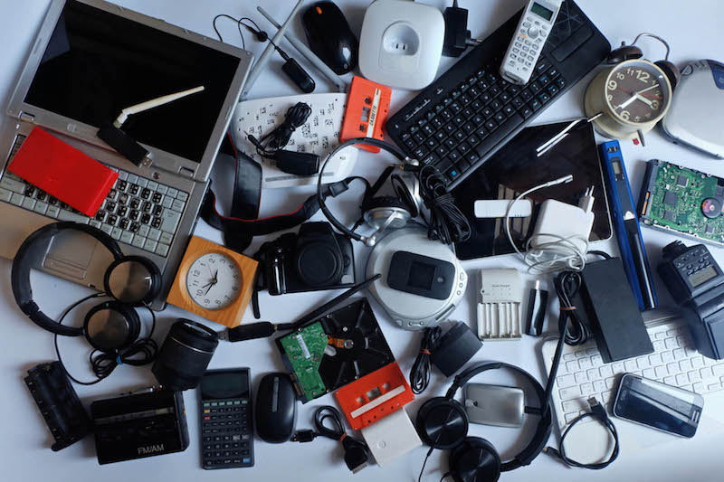 A pile of various old electronics from laptops, phones, keyboards, cameras, wires and more.