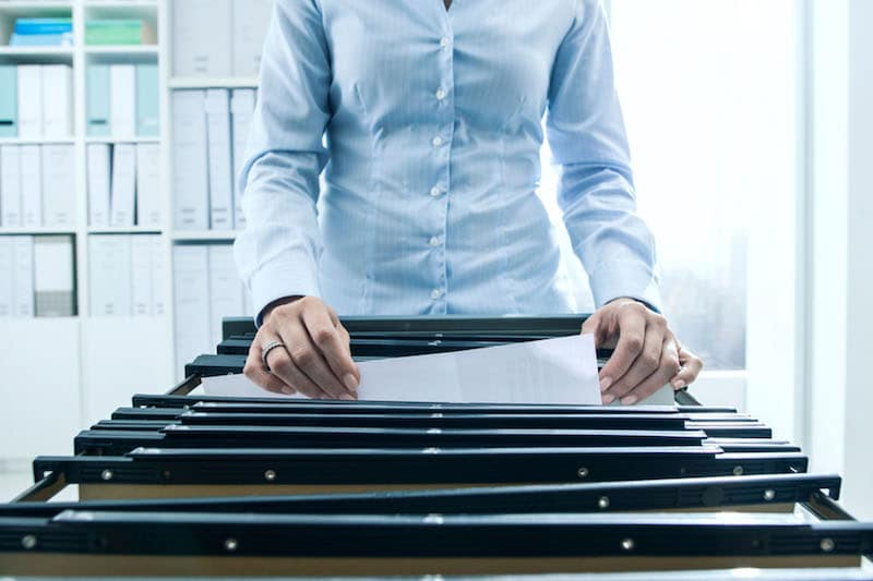Woman standing at open drawer of file cabinet looking through folders and files