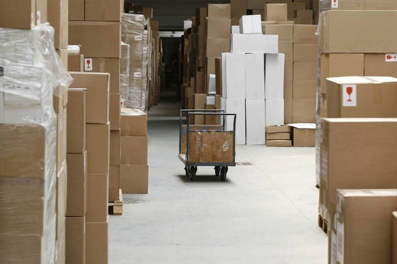 a warehouse full of cardboard boxes of varying sizes and a single empty cart in the middle of a space in the center without boxes